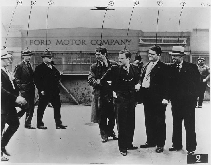 "After Walter Reuther became President of the United Auto Workers, he effectively ran the State of Michigan [details below]. This photo in the public domain is a labor movement icon. It shows Reuther (fifth from the left), in 1937early in his career as a union organizer. Reuther is about to be beaten by Ford Motor Company employees (called by the UAW ""goons."") Reuther recalled: ""Seven times they raised me off the concrete and slammed me down on it. They pinned my arms . . . and I was punched and kicked and dragged by my feet to the stairway, thrown down the first flight of steps, picked up, slammed down on the platform and kicked down the second flight. ""See Wikipedia: Battle of the Overpass."